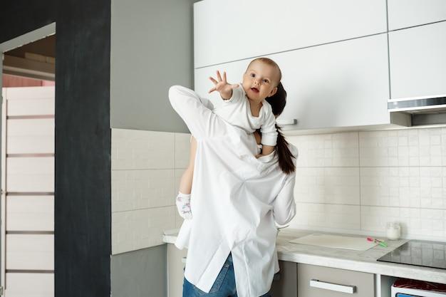 台所で小さな赤ちゃんと遊ぶ母