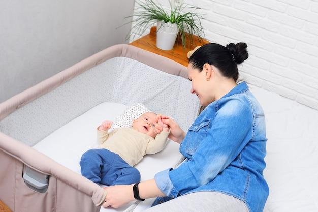 Мама играет с младенцем, который лежит на боковой кровати для новорожденного или в современном манеж.