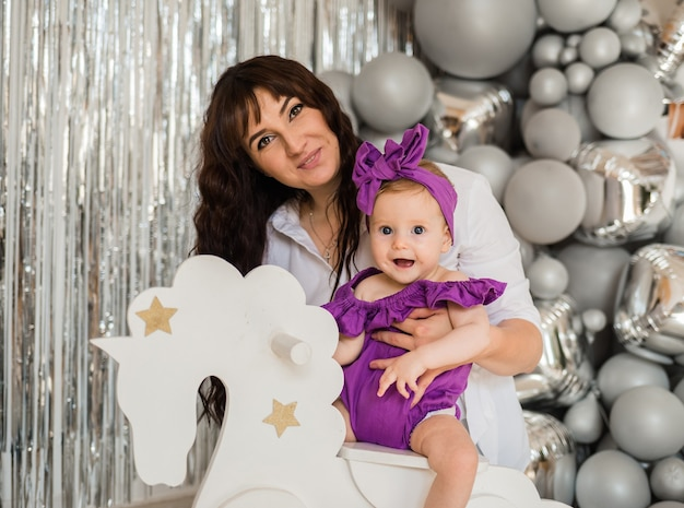 Mother plays with baby daughter sitting on a white horse on a gray foil background with balloons