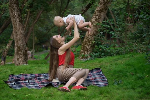 母は屋外で赤ちゃんと遊ぶ。楽しい愛情深い母親と赤ちゃん