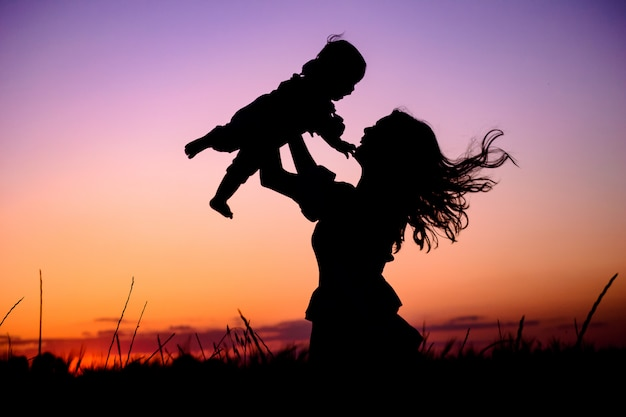 Mother plays with her baby in her arms under the rays of the sunset in a meadow