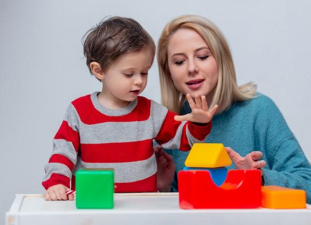 母はテーブルの上のサイコロで彼女の息子と遊ぶ