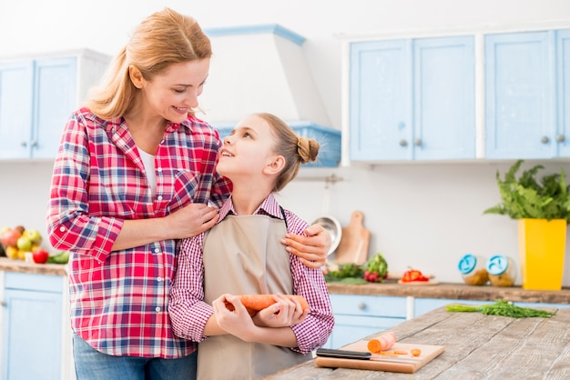 Mother pleasing her daughter holding carrot in hand