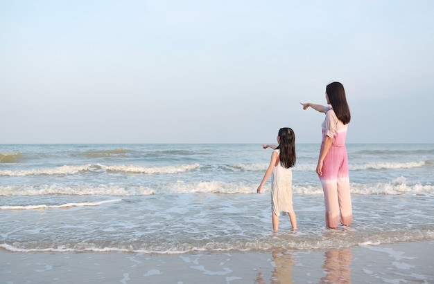 Mother pointing something with child girl looking in the sea