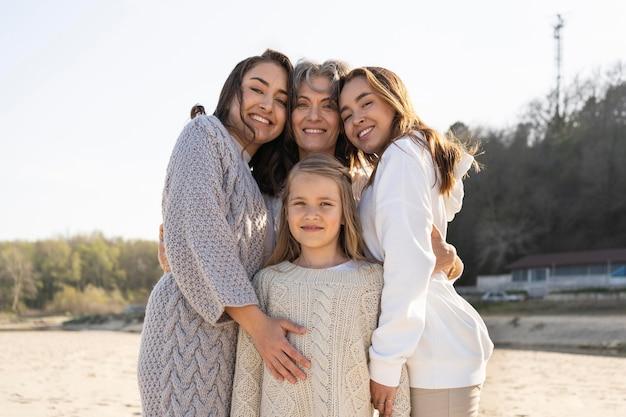 Мать позирует с дочерьми на пляже Premium Фотографии