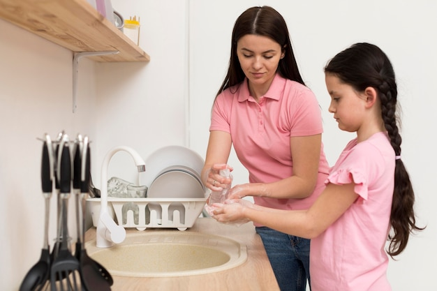 女の子のための消毒剤を注ぐ母