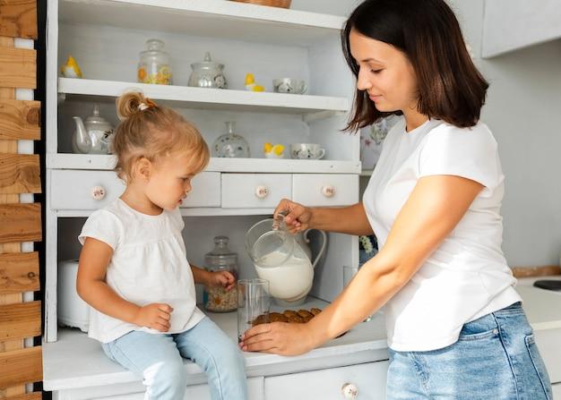 Мать наливает молоко для своей маленькой дочери