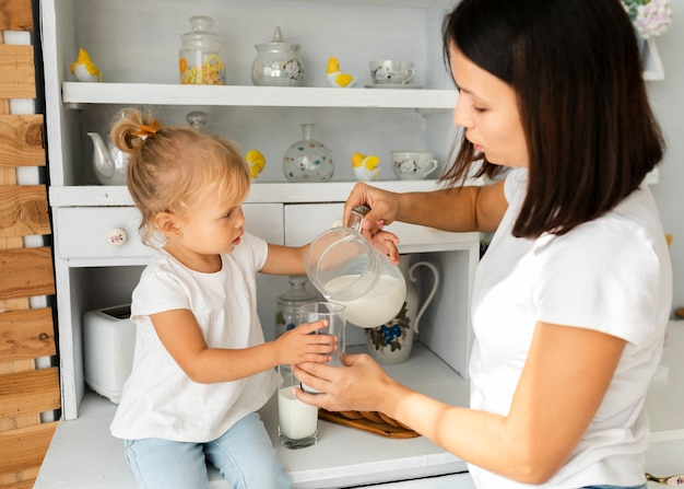 Mother pouring milk for her lovely daughter