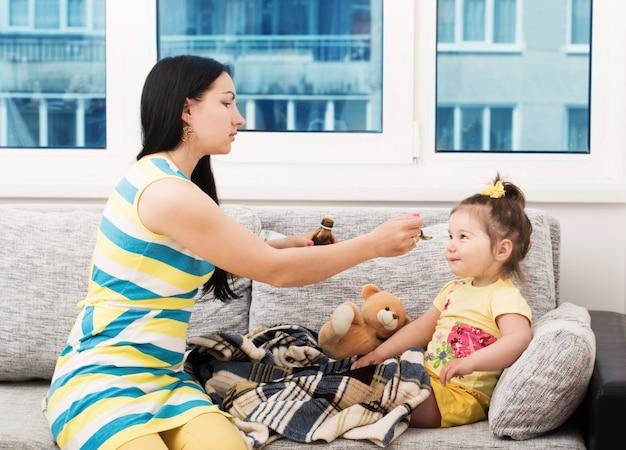 彼女の小さな女の子の咳を和らげるためにおいしいシロップを注ぐ母