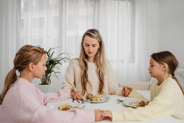 Мать молится с детьми за обеденным столом