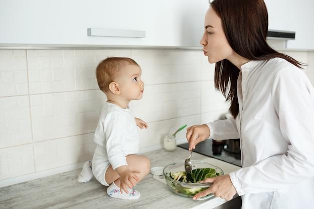 母親が赤ちゃんがカウンターに座っている間に食事を準備する