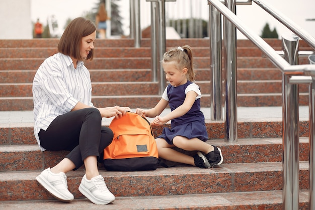 Mother prepare little daughter to school