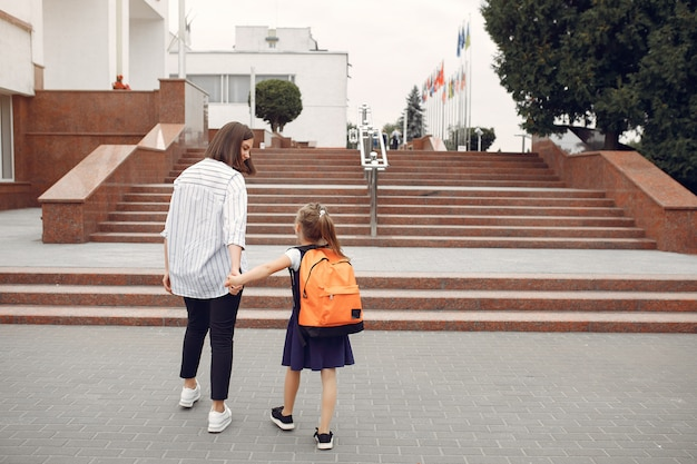 Mother prepare little daughter to school