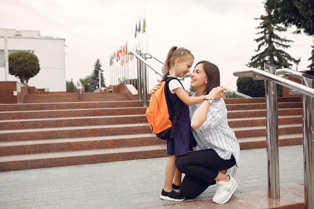 Мать готовит маленькую дочь к школе
