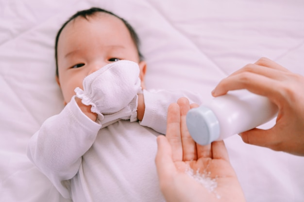 Mother preparing baby powder in her hand and 2 months old baby boy on bed.