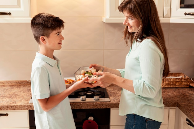 Mother preparing food in the kitchen with son