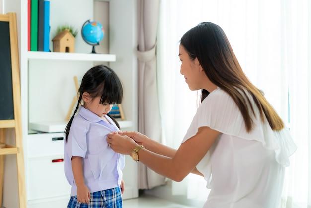Mother preparing kindergarten student uniform to her little daughter for school getting ready for school