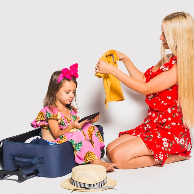 Mother preparing luggage with daughter watching tablet