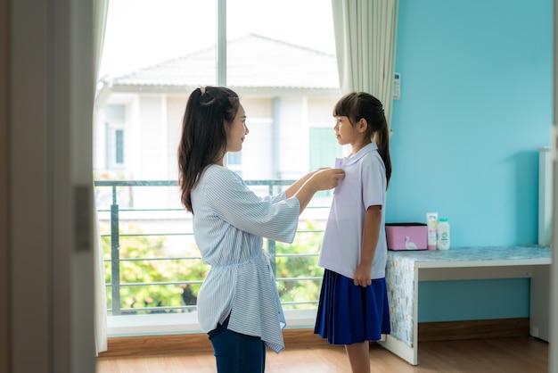 母は自宅のリビングルームで学校の彼女の小さな娘に小学生制服を準備します。
