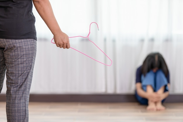 Mother punishing her daughter, holding clothes hanger
