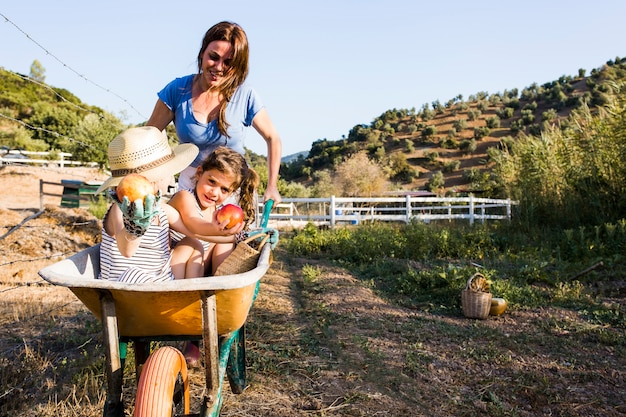 Mother pushing her daughters in wheelbarrow at field