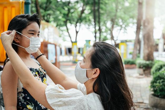 Мать надевает на лицо дочери защитную маску для защиты от вспышки коронавируса в деревенском парке, чтобы подготовиться к посещению школы. обратно в школу концепции.