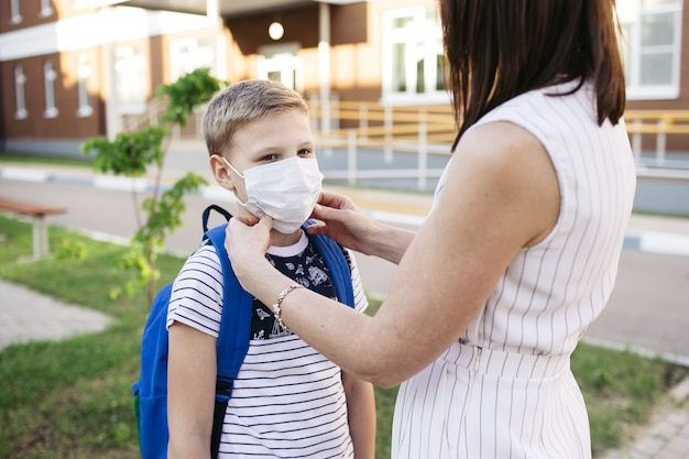母親は、学校に行く準備をするために、covid-19またはコロナウイルスの発生を保護するために息子の顔に安全マスクを付けます。学校のコンセプトに戻ります。コロナウイルスを防ぐための医療用マスク。