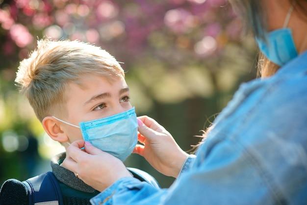 母は息子に屋外で顔の保護マスクを置きます。コロナウイルス、病気、感染症、検疫、医療用マスク、covid-19。