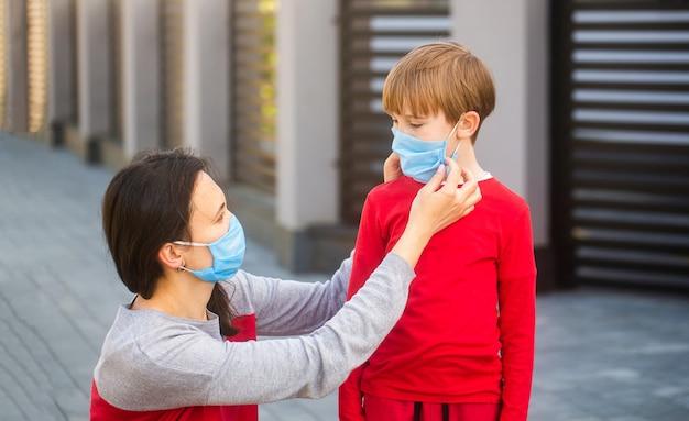 母は息子に屋外で顔の防護マスクを置く