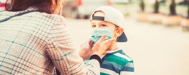Мать надевает сыну стерильную медицинскую маску. мать и ребенок носят маску во время коронавируса, вспышки гриппа. мама надевает на сына медицинскую маску. ребенок и мама в медицинской маске на прогулке