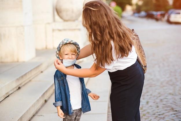 母は屋外で小さな子供のために医療用マスクを着用します。コロナウイルスと実生活。コロナウイルスを防ぐための医療用マスク。コロナウイルス検疫。散歩中の家族。
