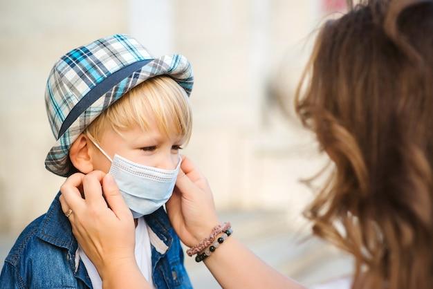 母は屋外で幼い息子のために医療用マスクを着用します。コロナウイルスと実生活。コロナウイルスを防ぐための医療用マスク。コロナウイルス検疫。散歩中の家族。