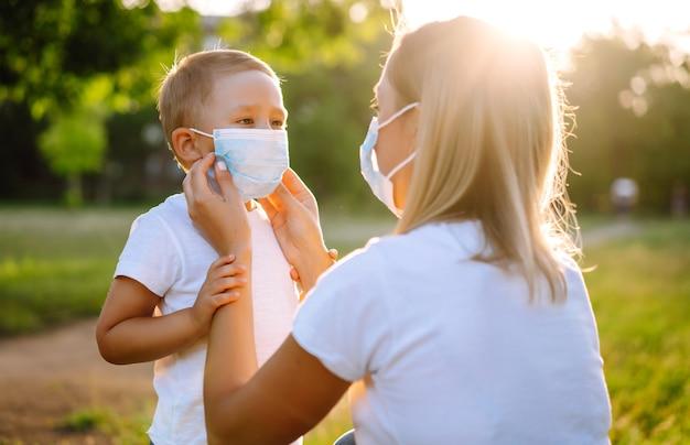 母親は公園covid2019で子供滅菌医療マスクを着用します