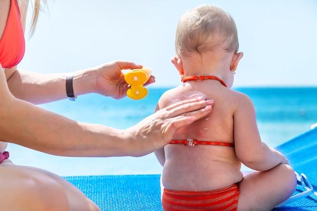 母親が赤ちゃんに日焼け止めを塗る