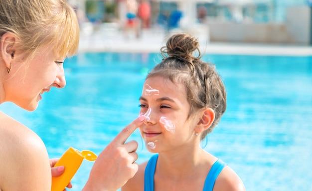 母はプールのそばの娘の顔に日焼け止めを置きます
