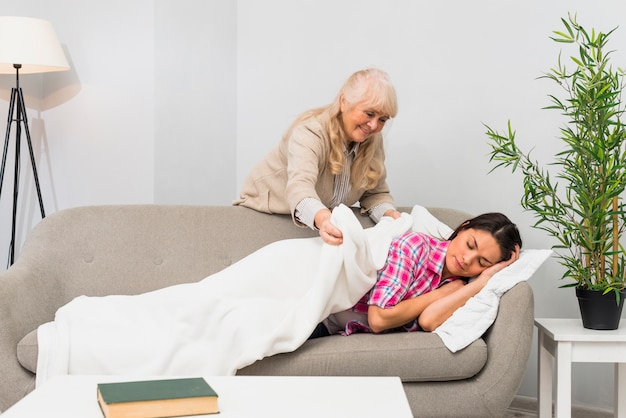 Mother putting blanket over her young adult daughter sleeping on sofa