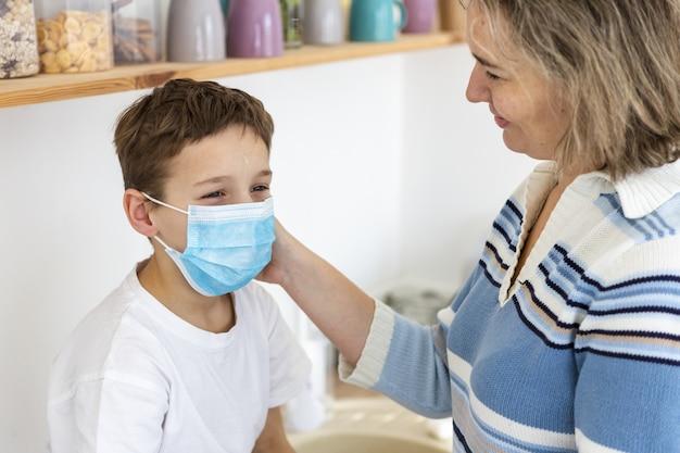 어머니는 그녀의 아이에 의료 마스크를 씌우고