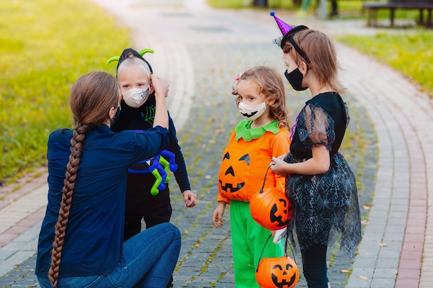 Mother putting protective face mask on her child during covid19 pandemic at halloween