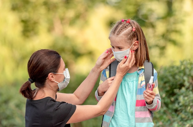 Mother putting protective mask on little daughter before going back to school