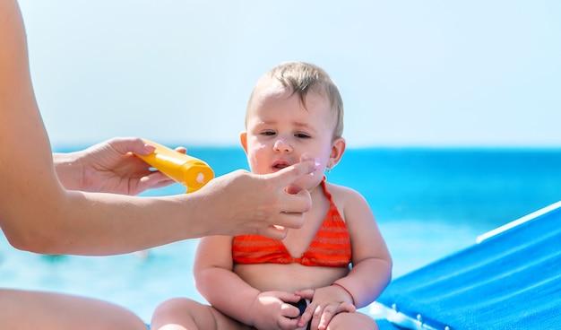 赤ちゃんに日焼け止めを塗る母親