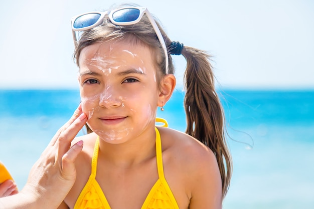 ビーチで娘の顔に日焼け止めを塗る母