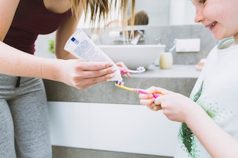 Mother putting toothpaste on brush of daughter