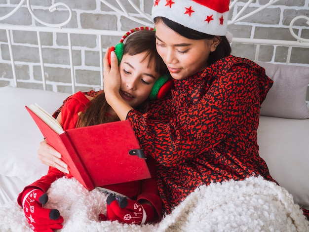 Mother read a book to her daughter on christmas day,happy family concept