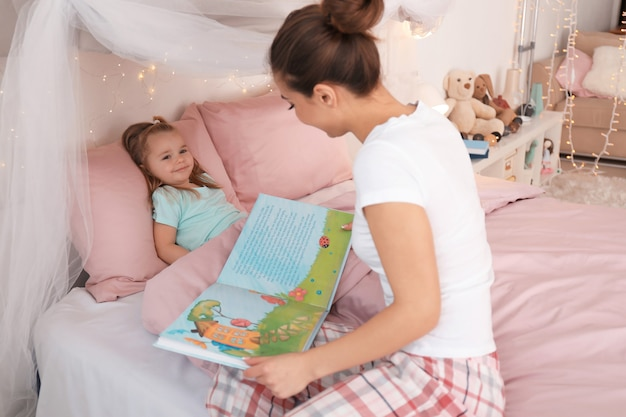 Мать читает сказку на ночь своей маленькой дочери дома