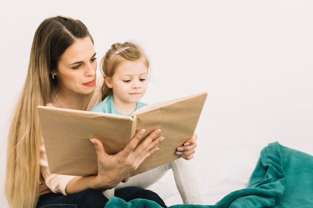 Mother reading book to cute girl on bed