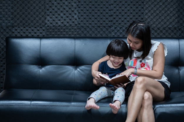Mother reading book for her child on bed, read cartoon book, storytelling with children