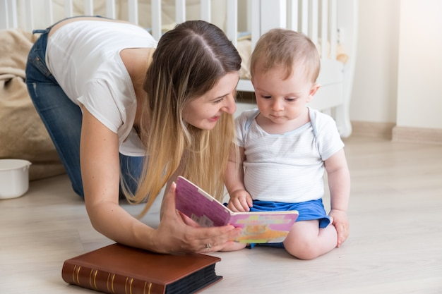 거실 바닥에 있는 10개월 된 아기에게 책을 읽어주는 어머니
