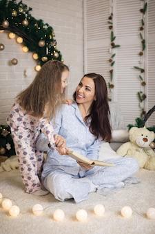 自宅のクリスマスツリーの近くで彼女の小さなかわいい娘に本を読んでいる母