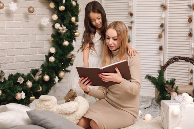 自宅のクリスマスツリーの近くで彼女の小さな娘に本を読んでいる母