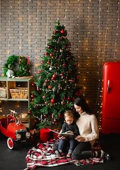 彼女の子供にクリスマスの物語を読んでいる母